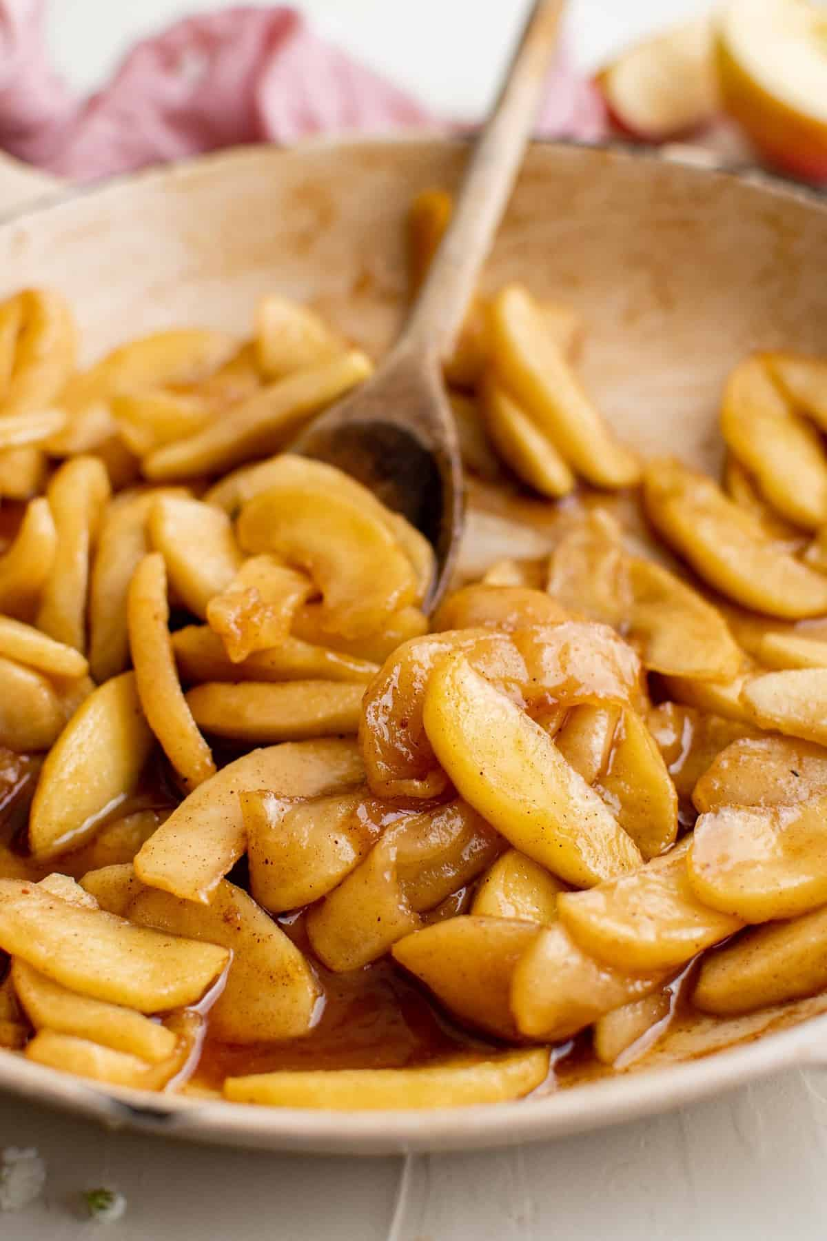 Cooked apples in a frying pan with a wooden spoon.