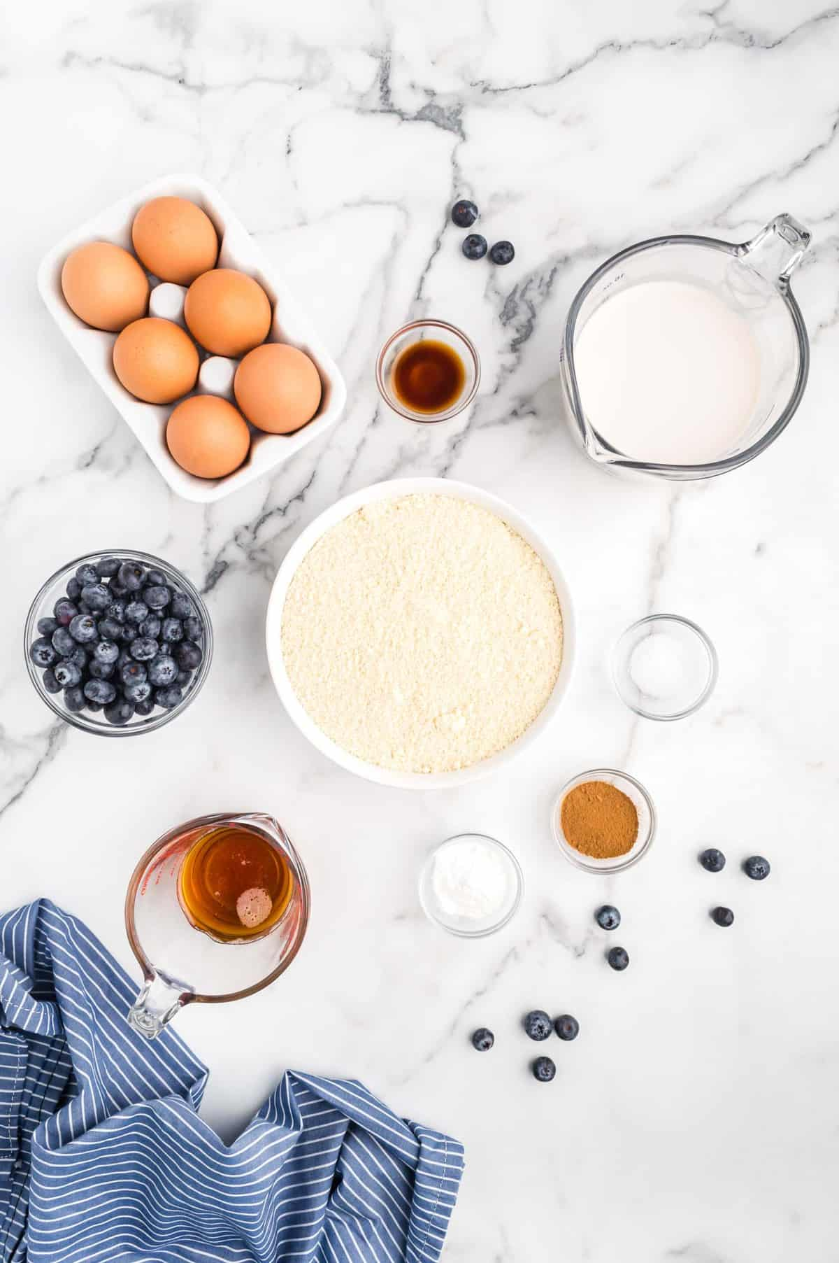 Overhead view of ingredients, including blueberries and brown eggs.