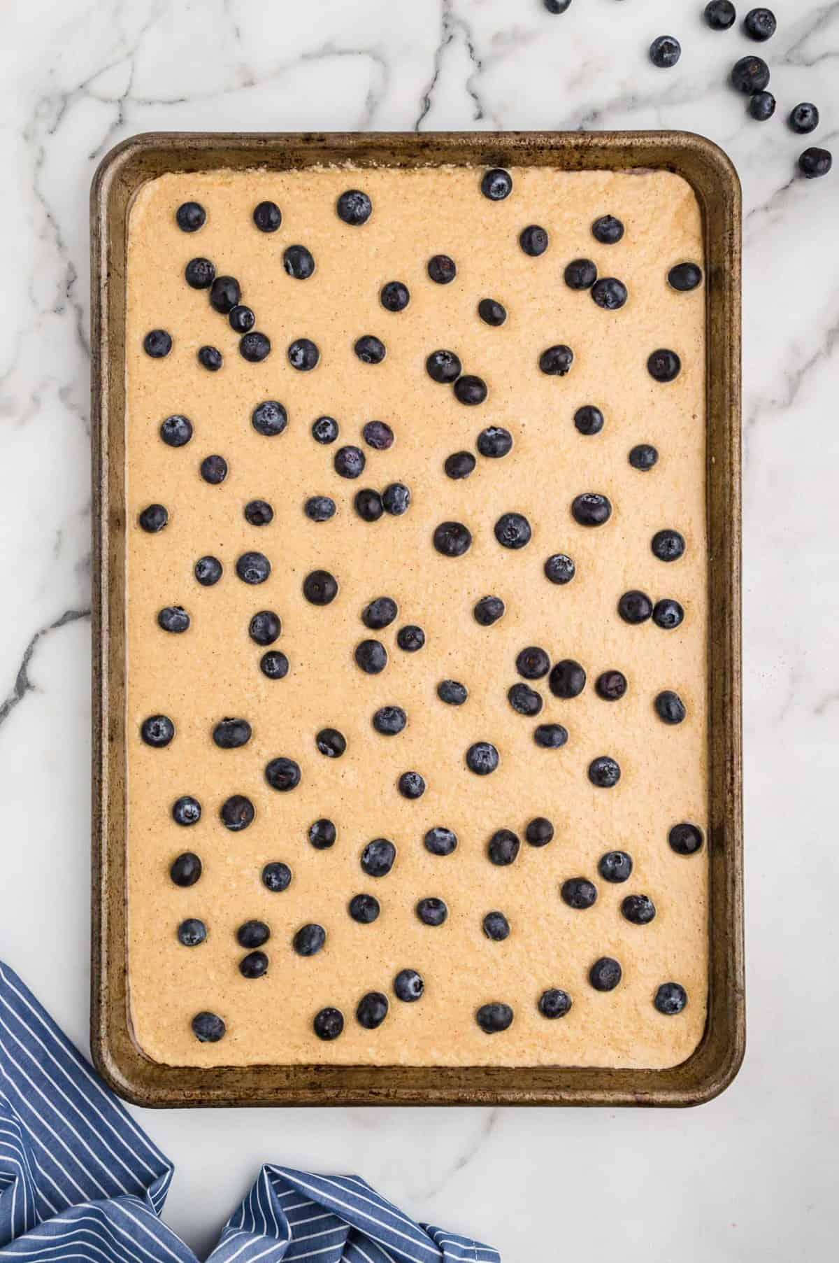 Unbaked sheet pan pancake with blueberries.