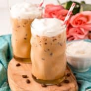Two iced vanilla lattes topped with whipped cream.