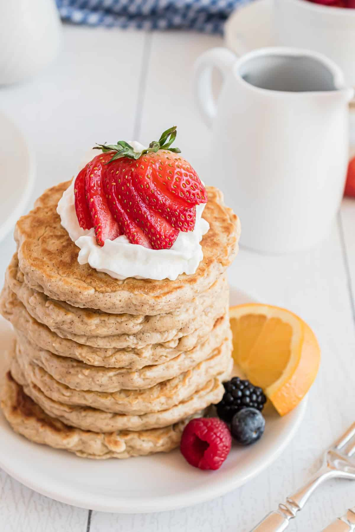 Oatmeal pancakes in a tall stack, topped with whipped cream and a strawberry.