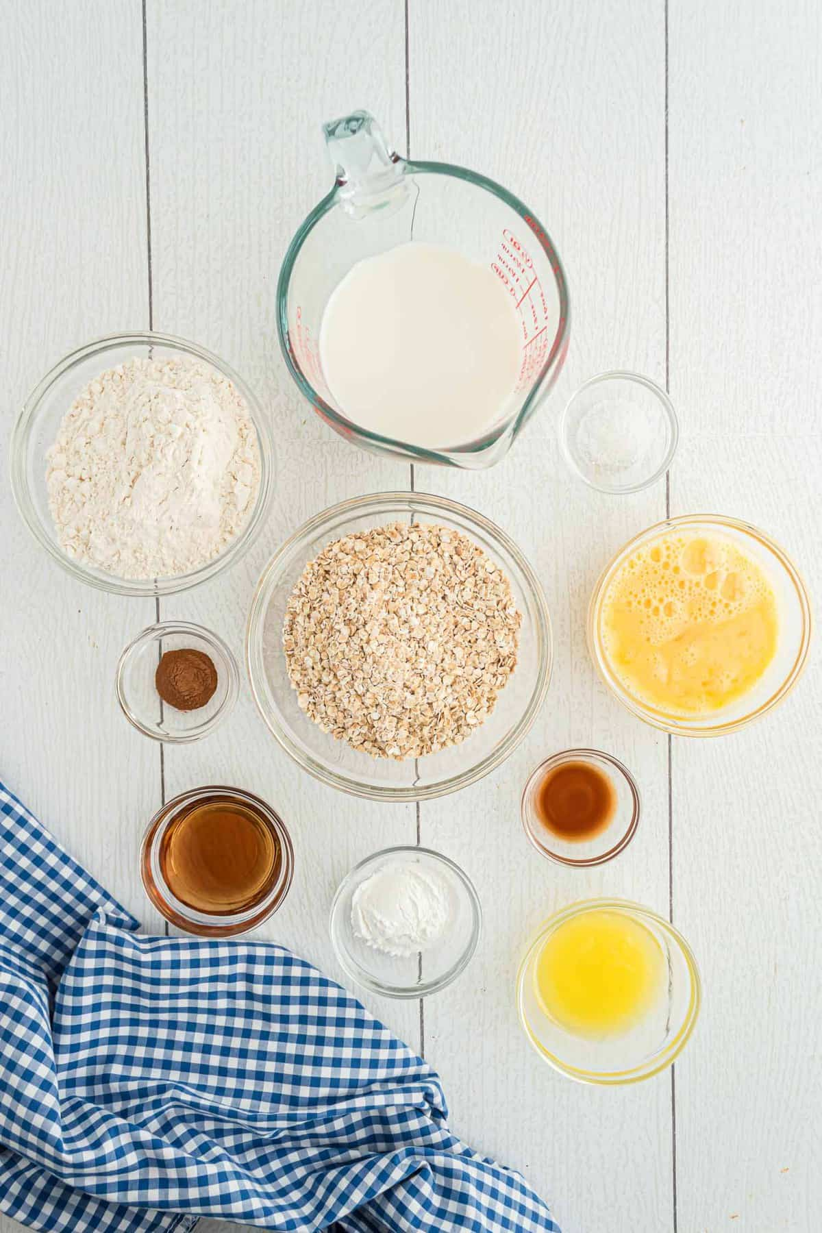 Overhead view of bowls of ingredients: oats, flour, butter, vanilla, cinnamon, and more.