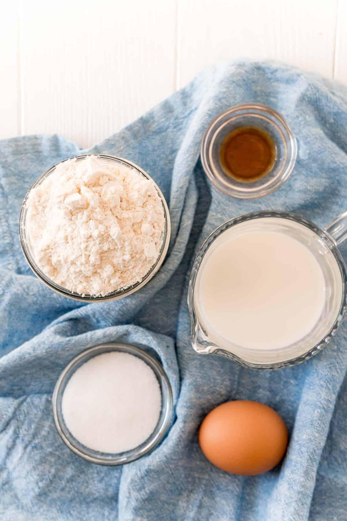 Overhead view of ingredients: Milk, bisquick, vanilla, sugar, egg.