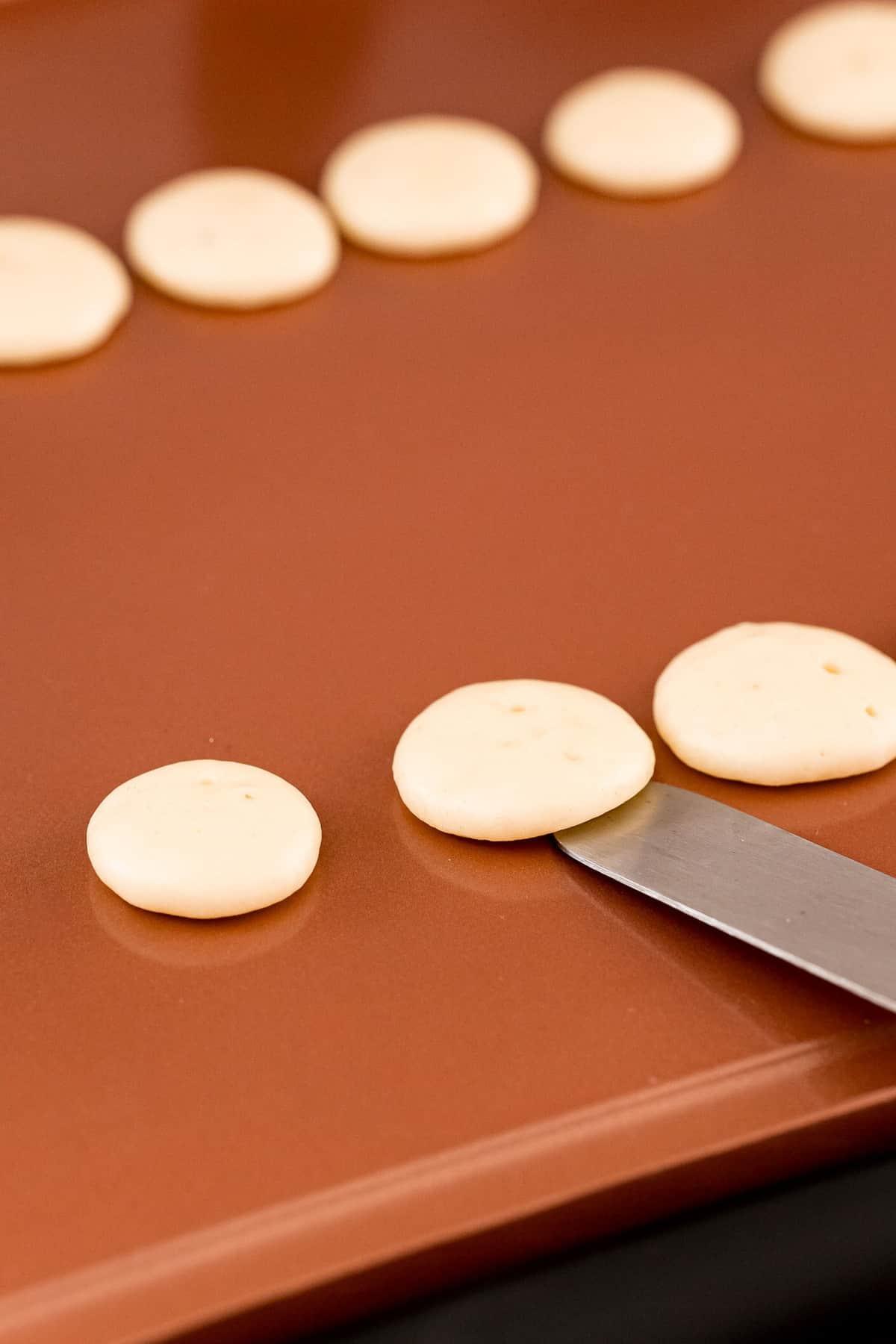 Offset spatula flipping mini pancakes.