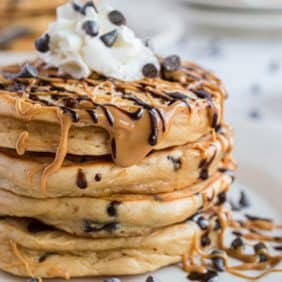 Stack of pancakes drizzled with peanut butter and chocolate.