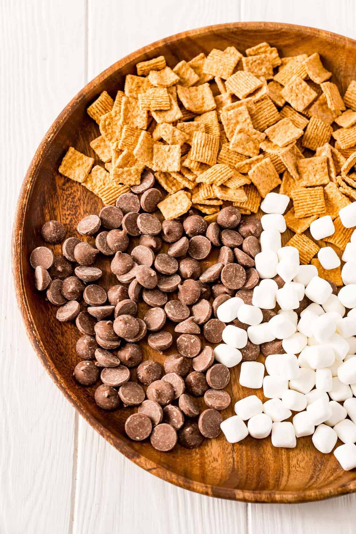 Golden graham cereal, chocolate chips, and marshmallows on large wooden tray.