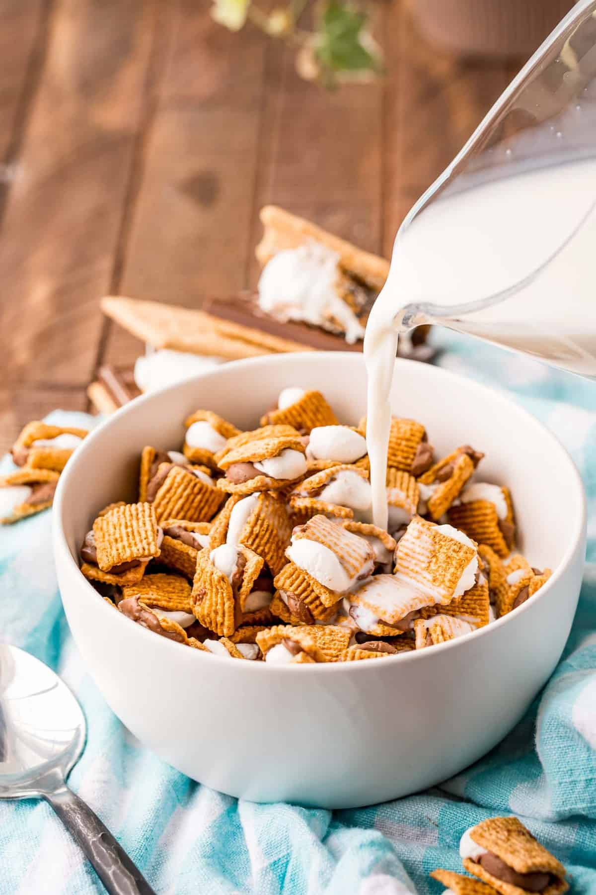 Milk being poured into a bowl of s'mores cereal.