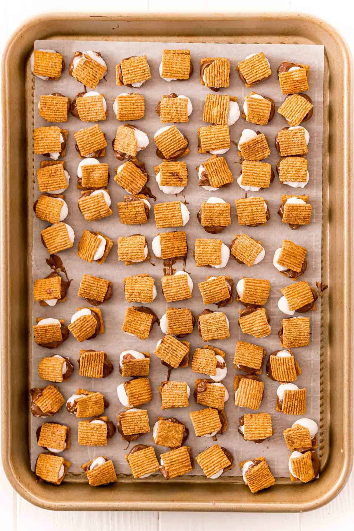 Tiny s'mores on a baking sheet.