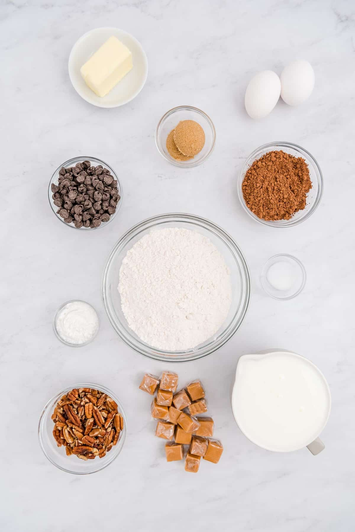Overhead view of bowls of ingredients including caramel, pecans, flour, cocoa powder.