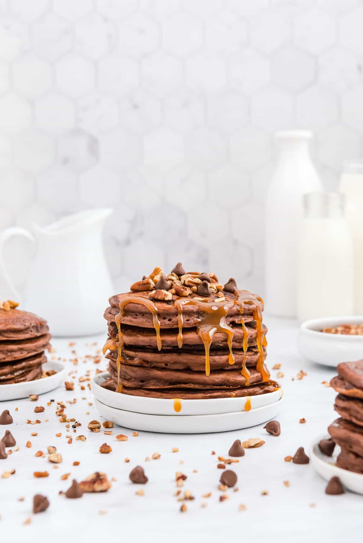 Stack of turtle pancakes with caramel, pecans, and chocolate chips.