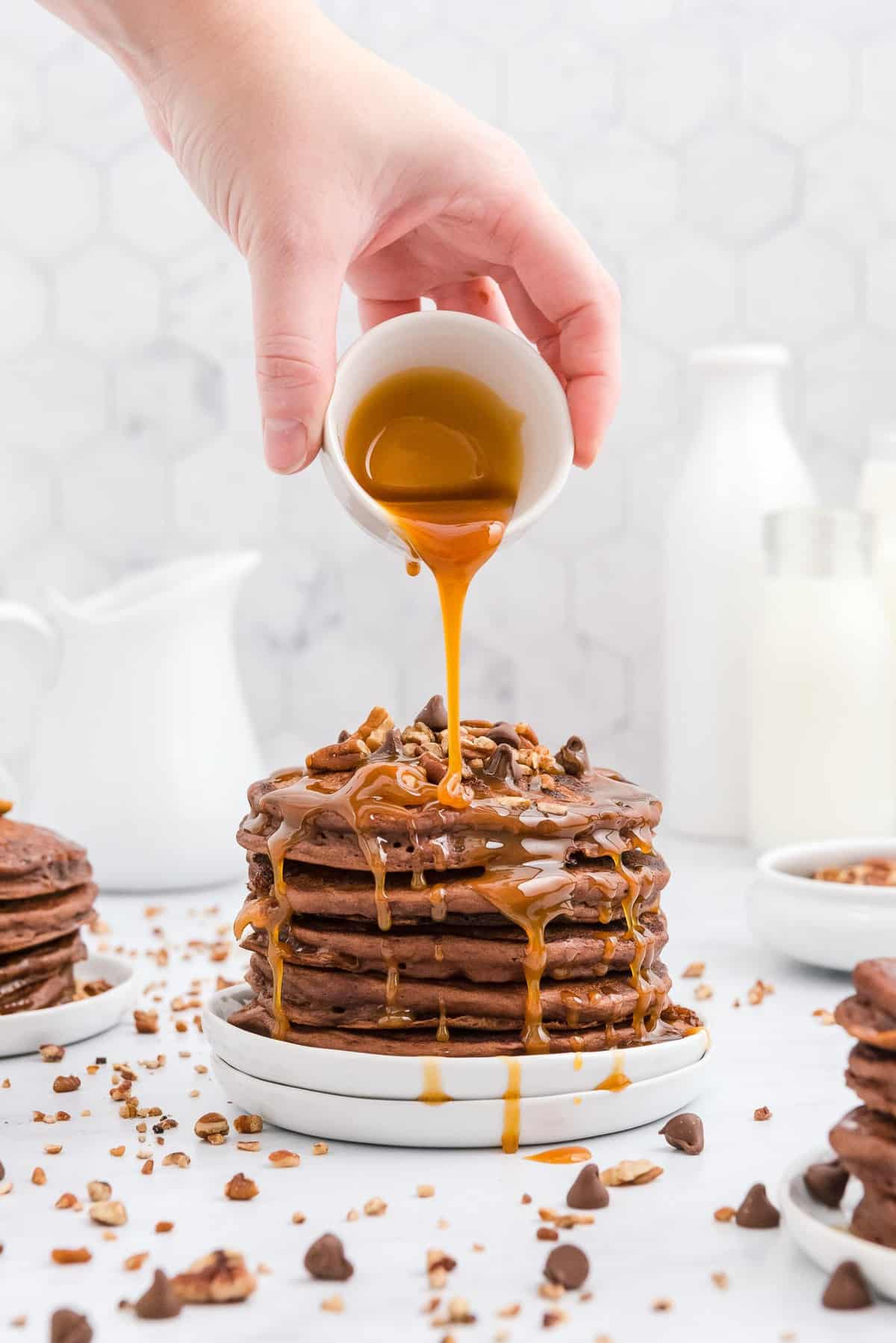 Caramel being poured on a stack of chocolate pancakes topped with pecans.