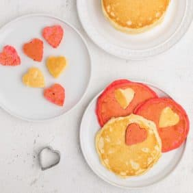 Red and white pancakes with heart-shaped cut outs.