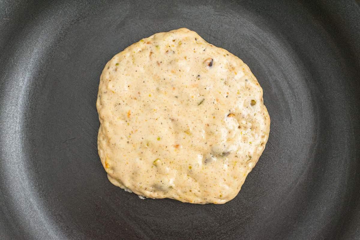 Half cooked pancake on a black skillet.
