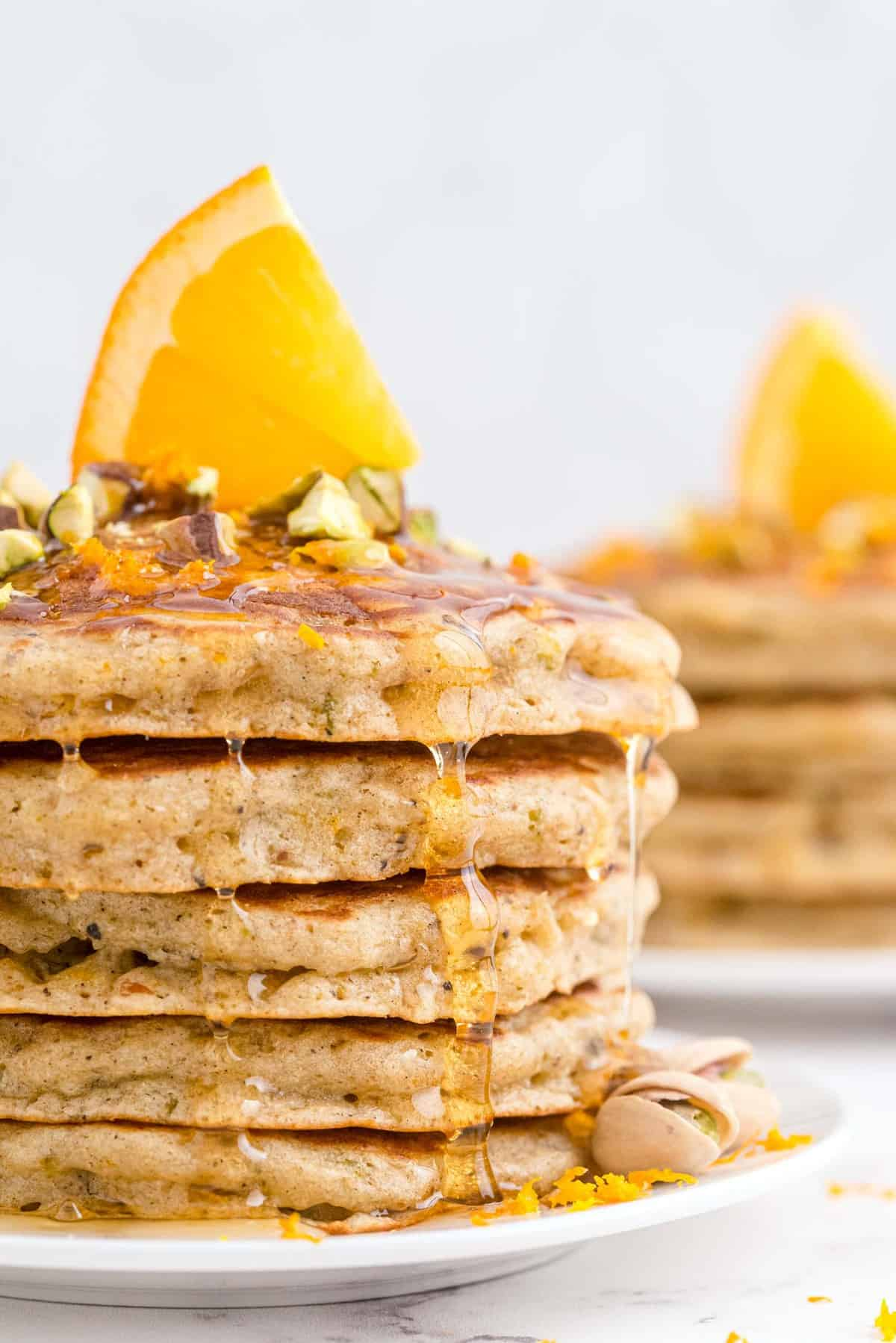 Stack of pancakes on a white plate, topped with pistachios, honey, and an orange slice.