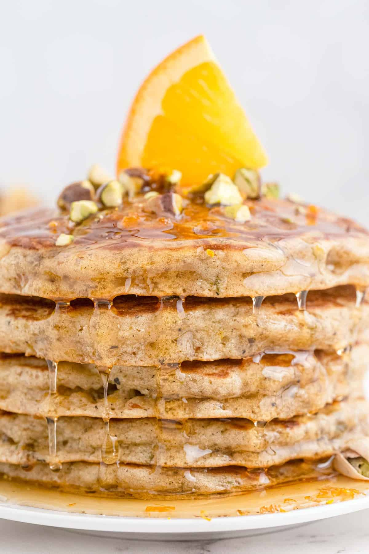 Close up of pancakes dripping with honey.