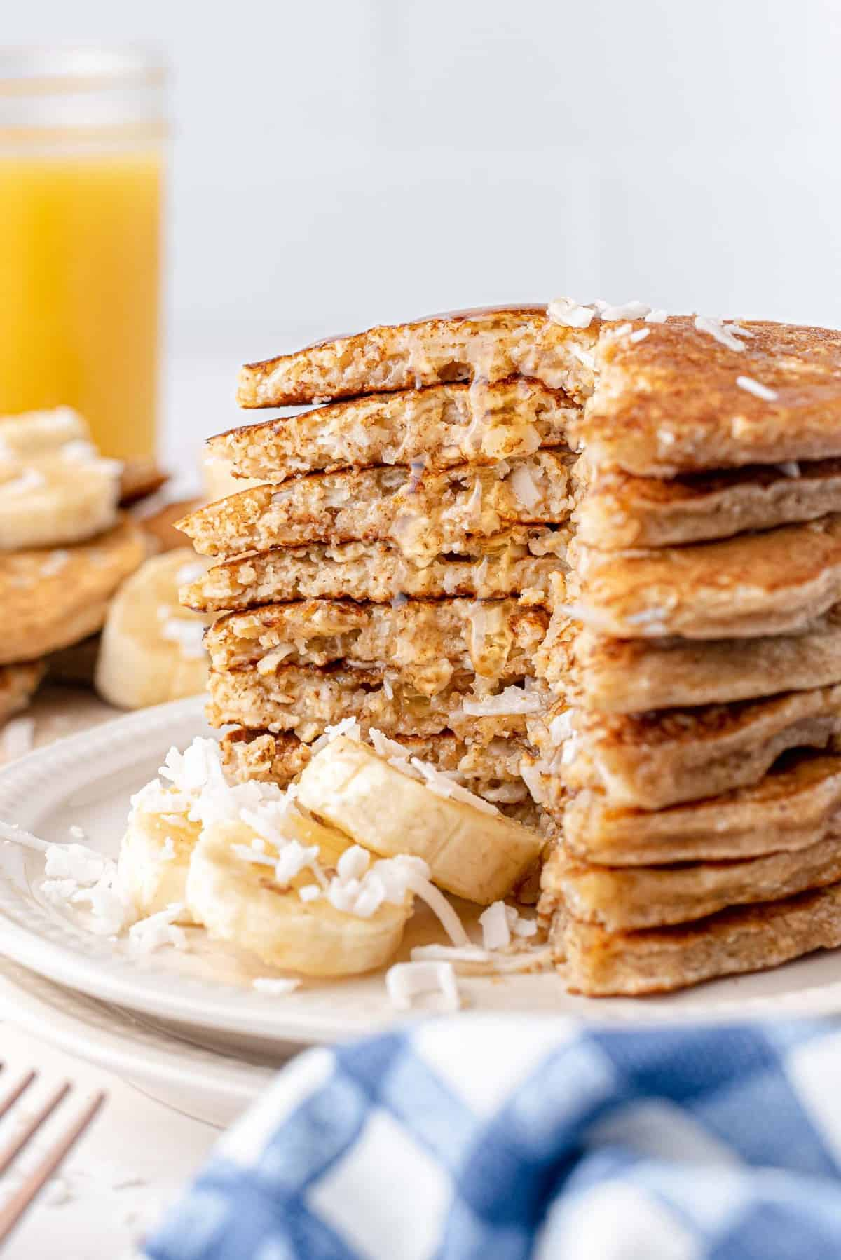 Tall stack of pancakes with banana slices.