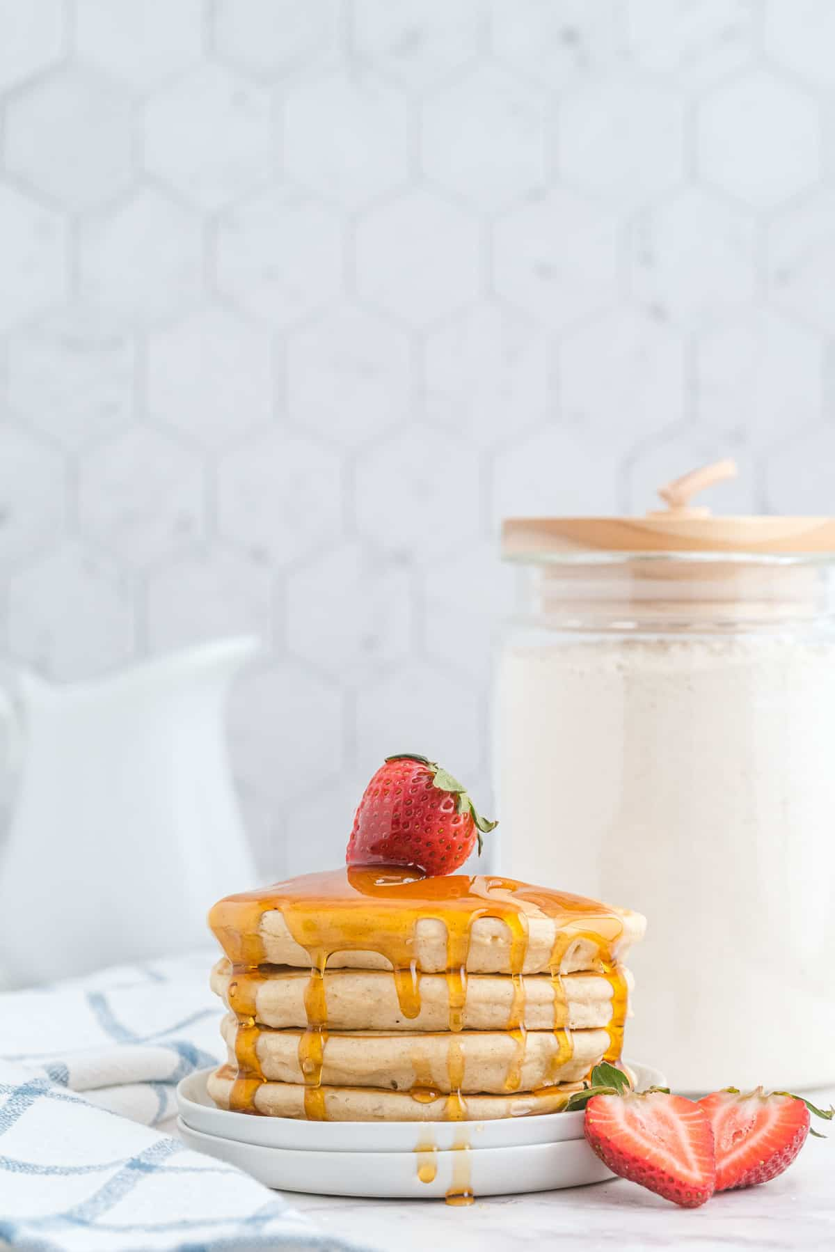 Stack of pancakes with syrup and strawberries, a canister of pancake mix in the background.