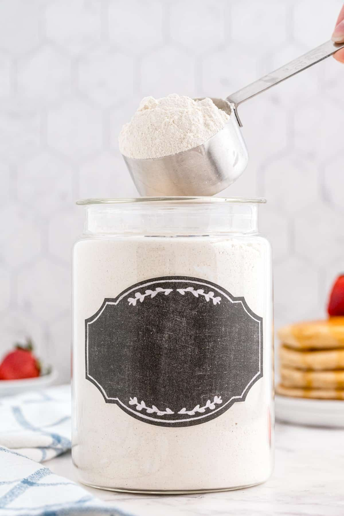Pancake mix being scooped out of a large jar with black label.