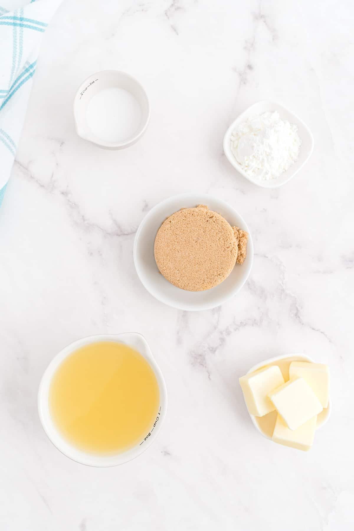 Overhead view of ingredients for rum sauce: Butter, brown sugar, pineapple juice, cornstarch, coconut cream.