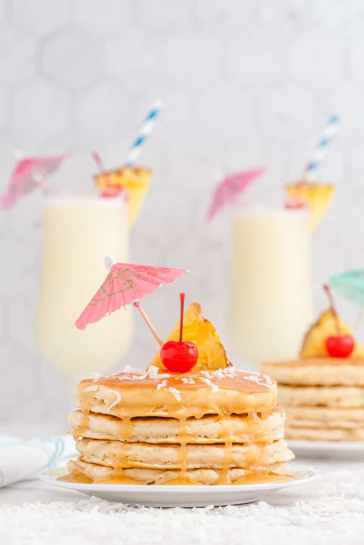 Pancakes with pina coladas in the backgorund.