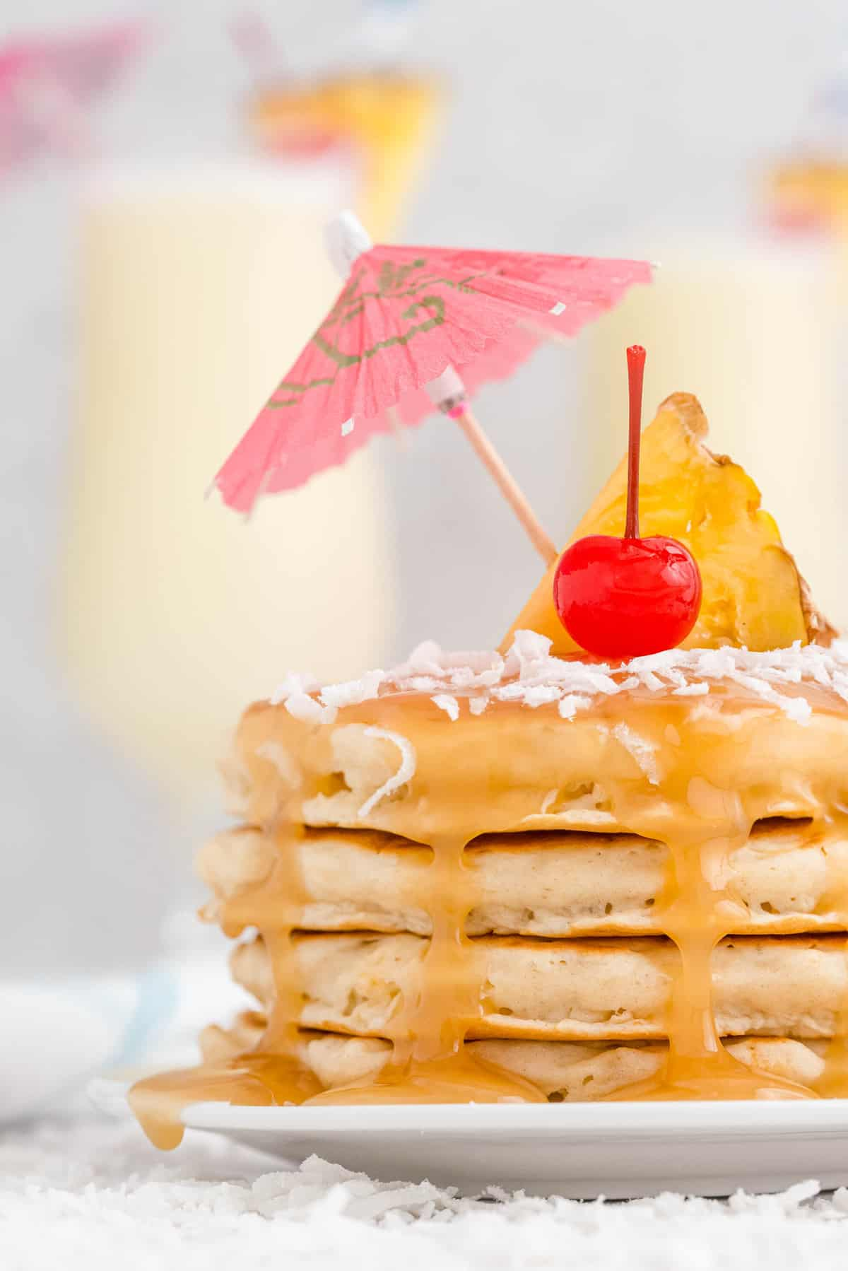 Stack of pancakes with caramel sauce, coconut, and a paper umbrella.