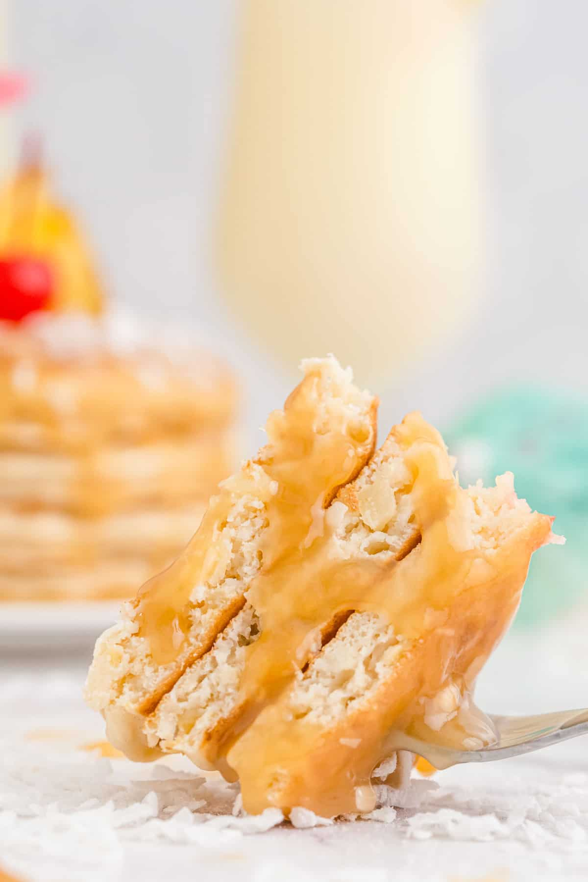 Cut pina colada pancakes on a fork, dripping with rum sauce.