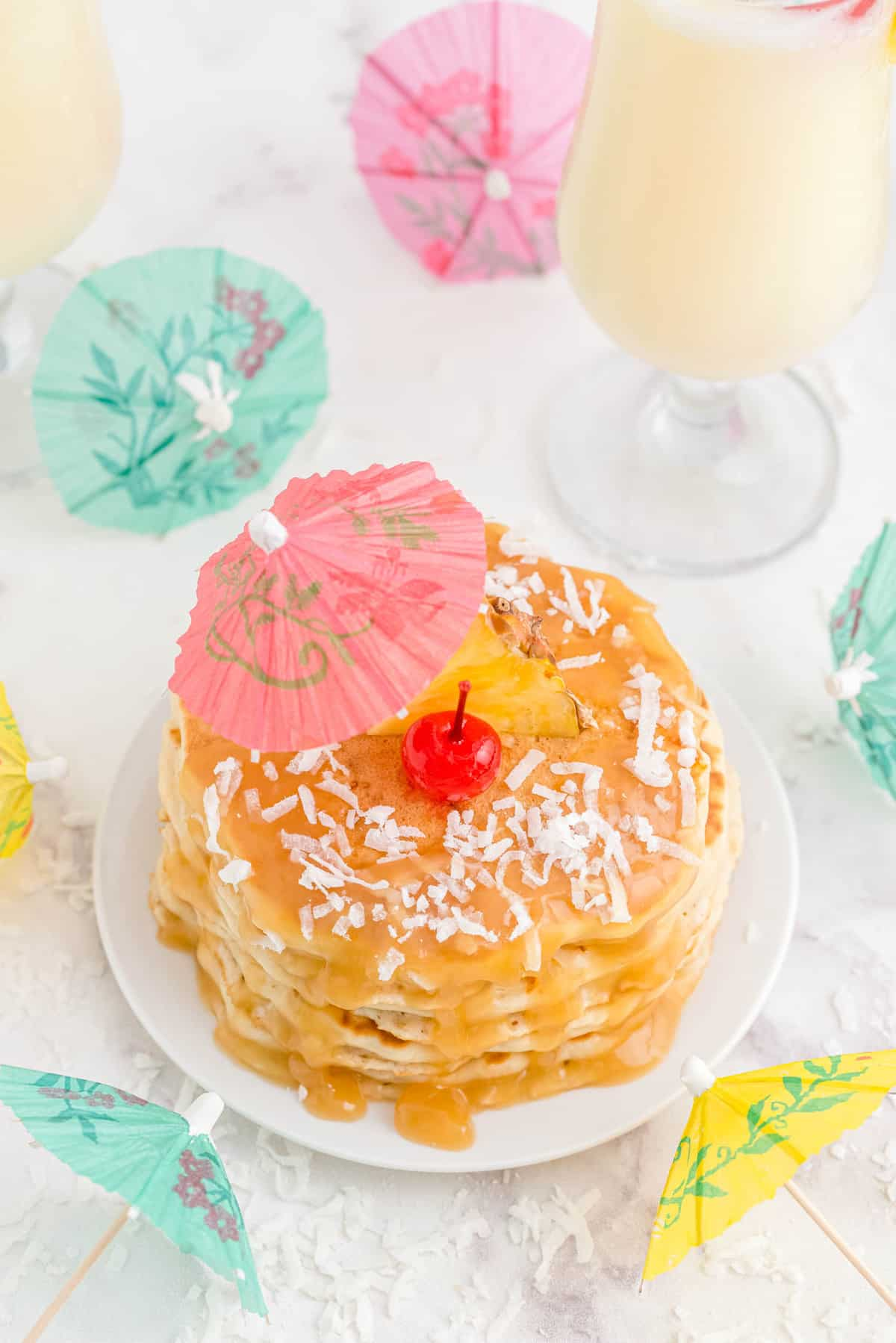 Pina colada pancakes from overhead, topped with coconut, a cherry, and a paper umbrella.