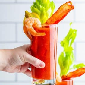 Hand holding a bloody mary cocktail with bacon, shrimp, okra, and celery.