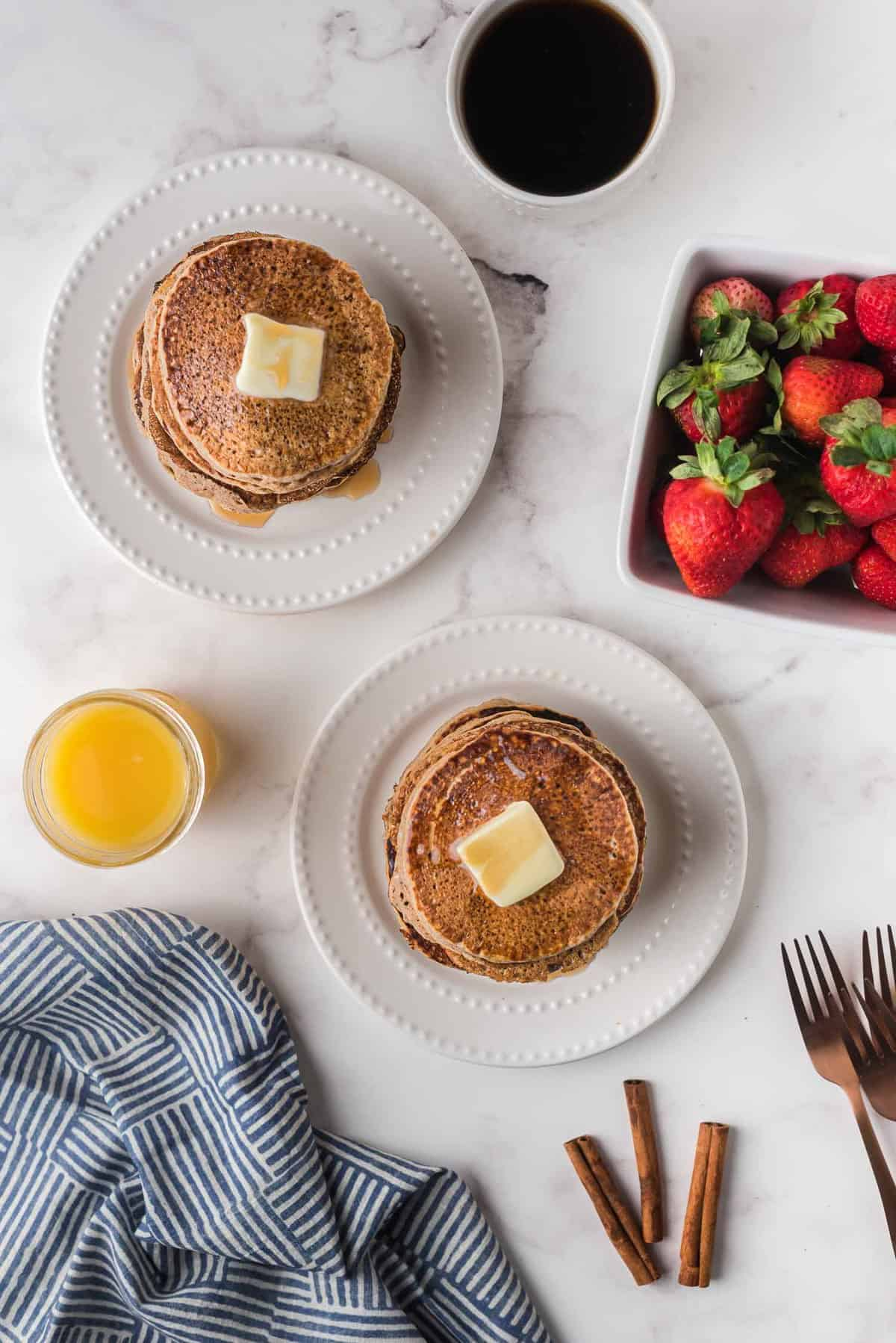 Overhead view of two plates of butter topped pancakes, with fruit, coffee, and orange juice nearby.