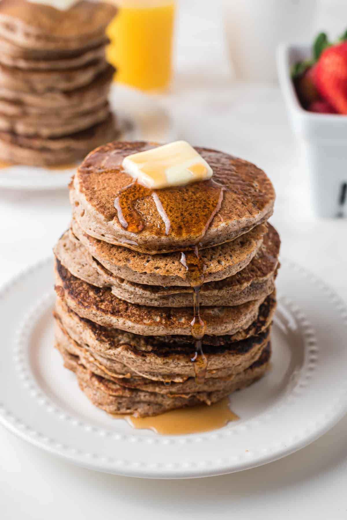 Tall stack of pancakes with butter and syrup.