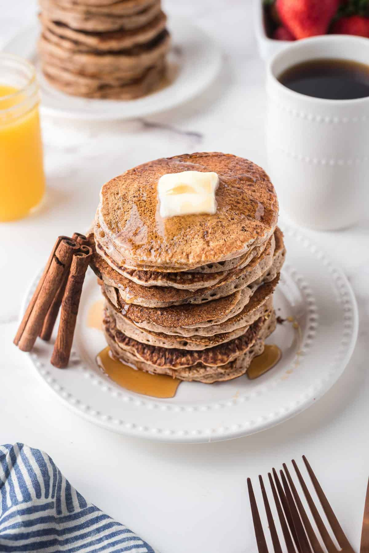 Large stack of pancakes with cinnamon sticks leaning against it.