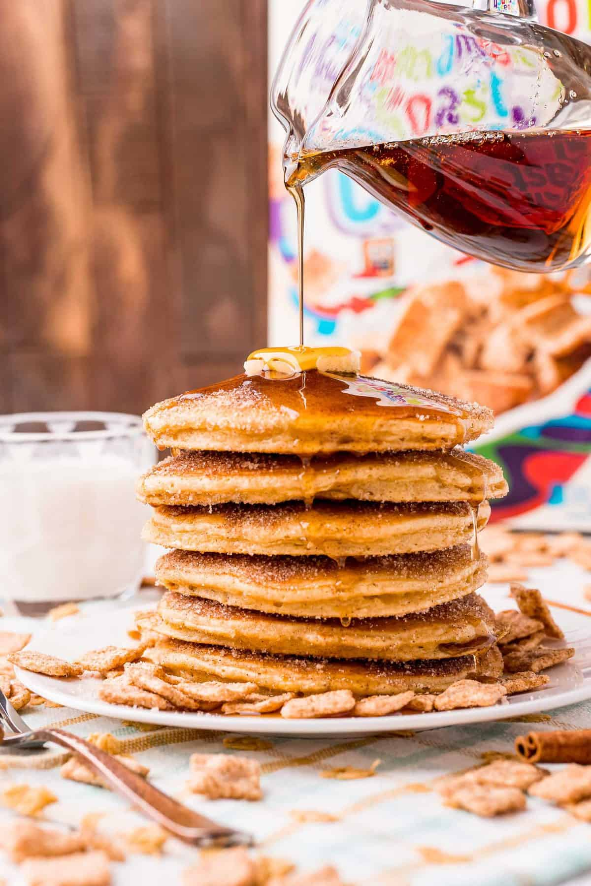 Syrup being poured on a tall stack of pancakes.