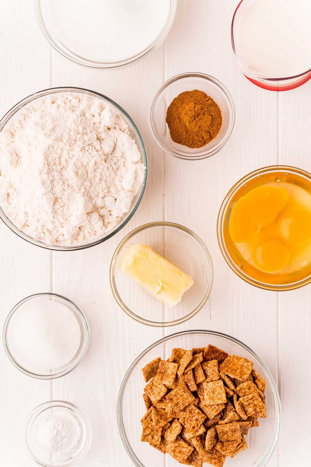 Overhead view of small glass bowls with ingredients, including cinnamon cereal, flour, butter, eggs, and cinnamon.