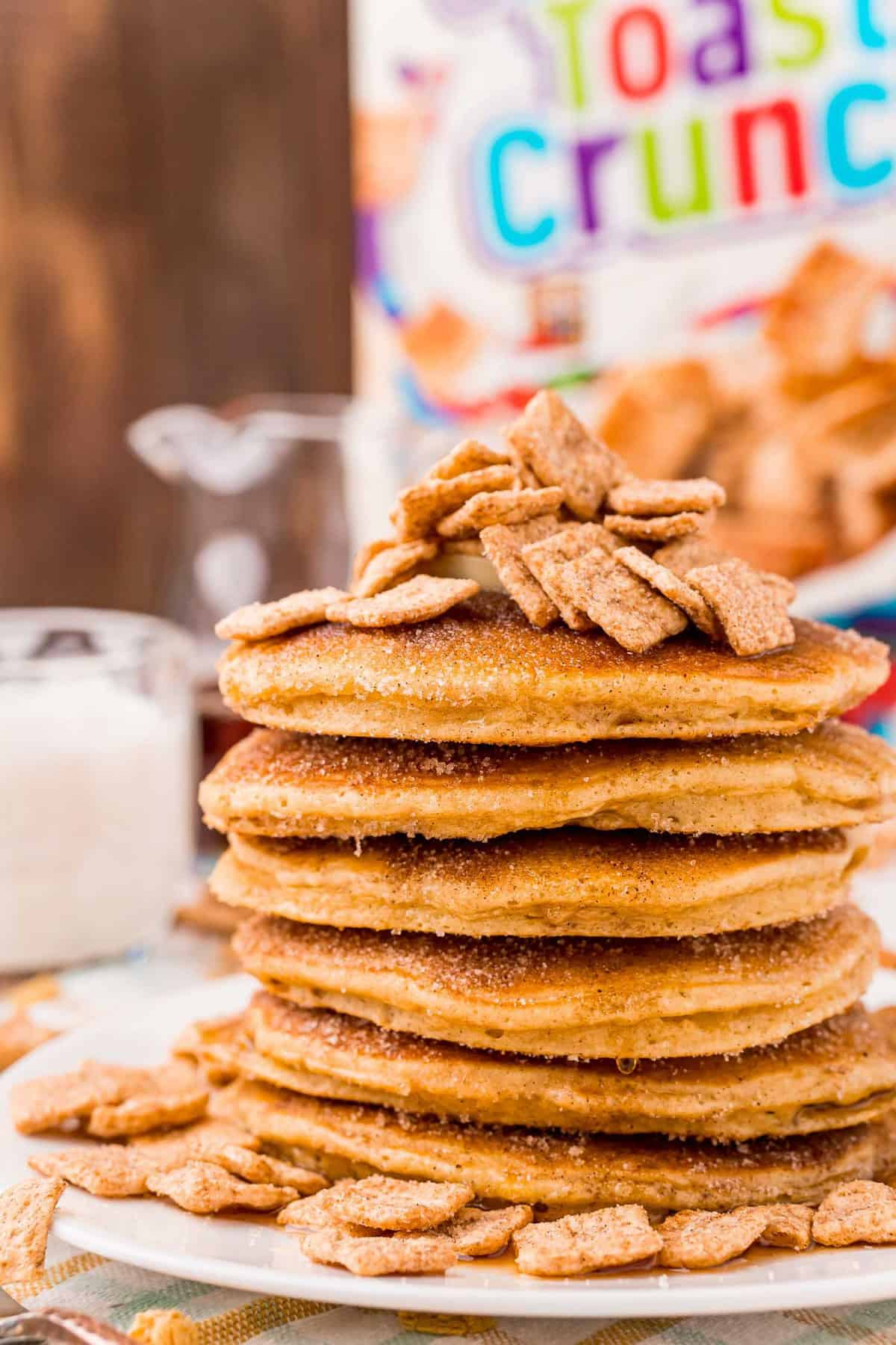 Tall stack of pancakes topped with cinnamon toast crunch cereal.
