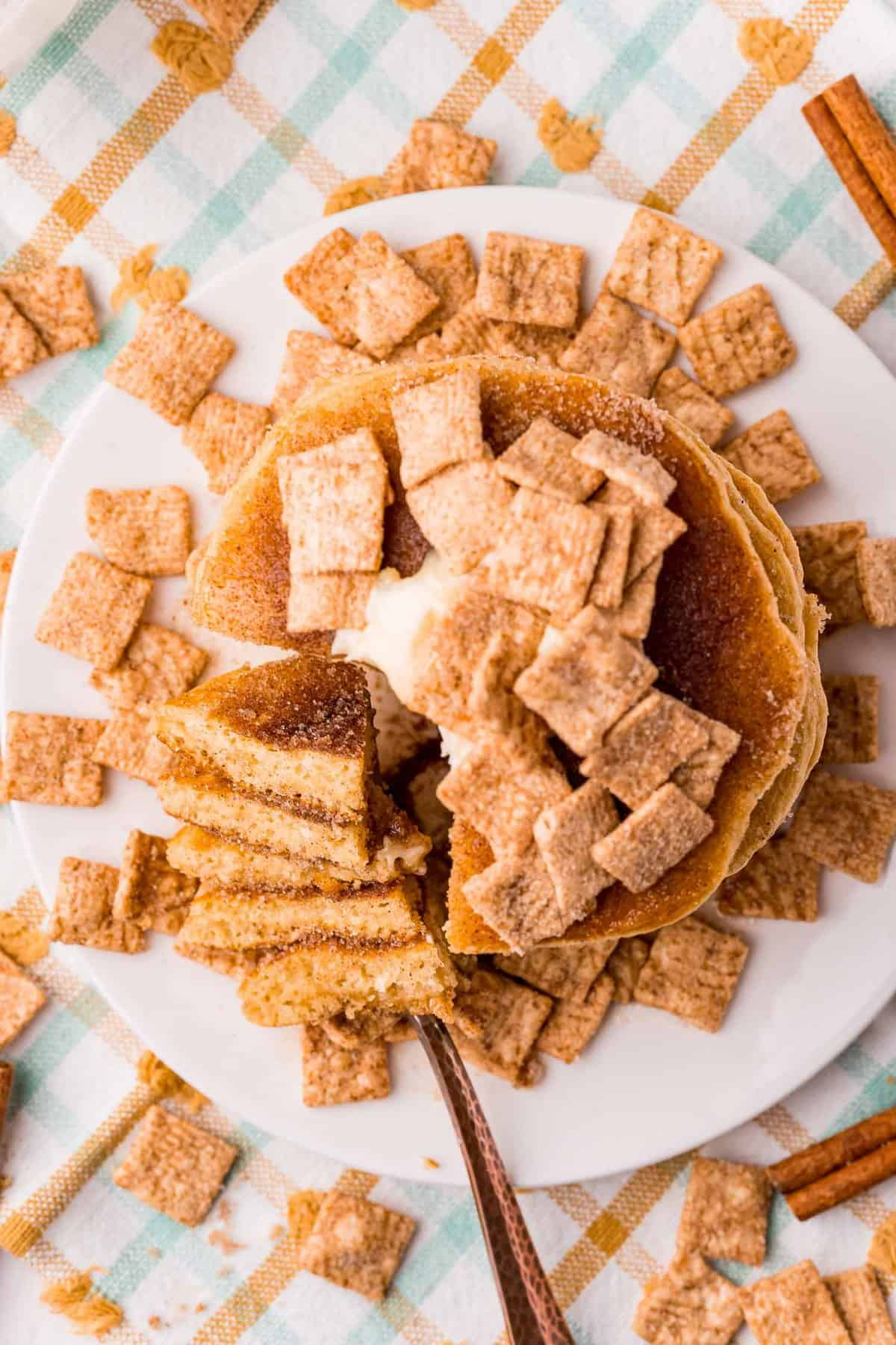 Overhead view of pancakes topped with cinnamon toast crunch cereal.
