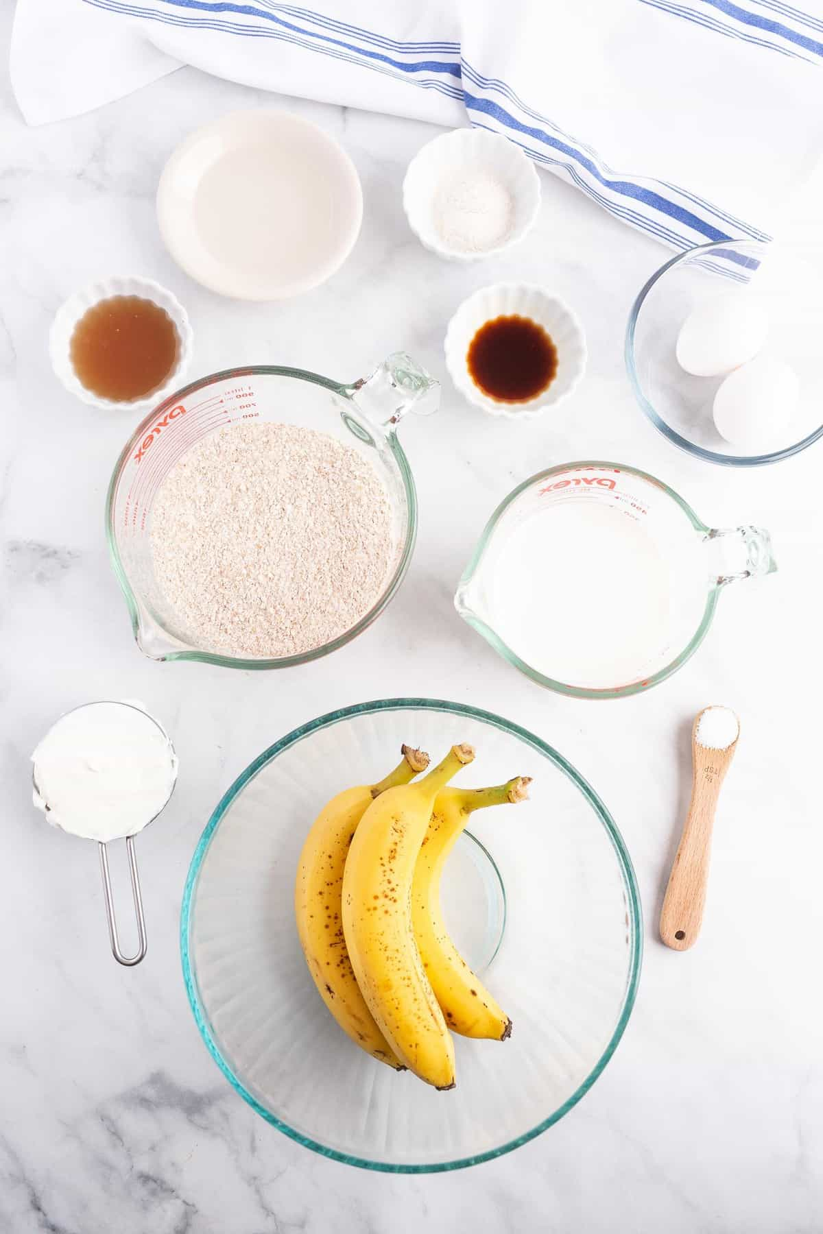 Overhead view of small glass bowls full of ingredients, including bananas, whole wheat flour, eggs, and more.