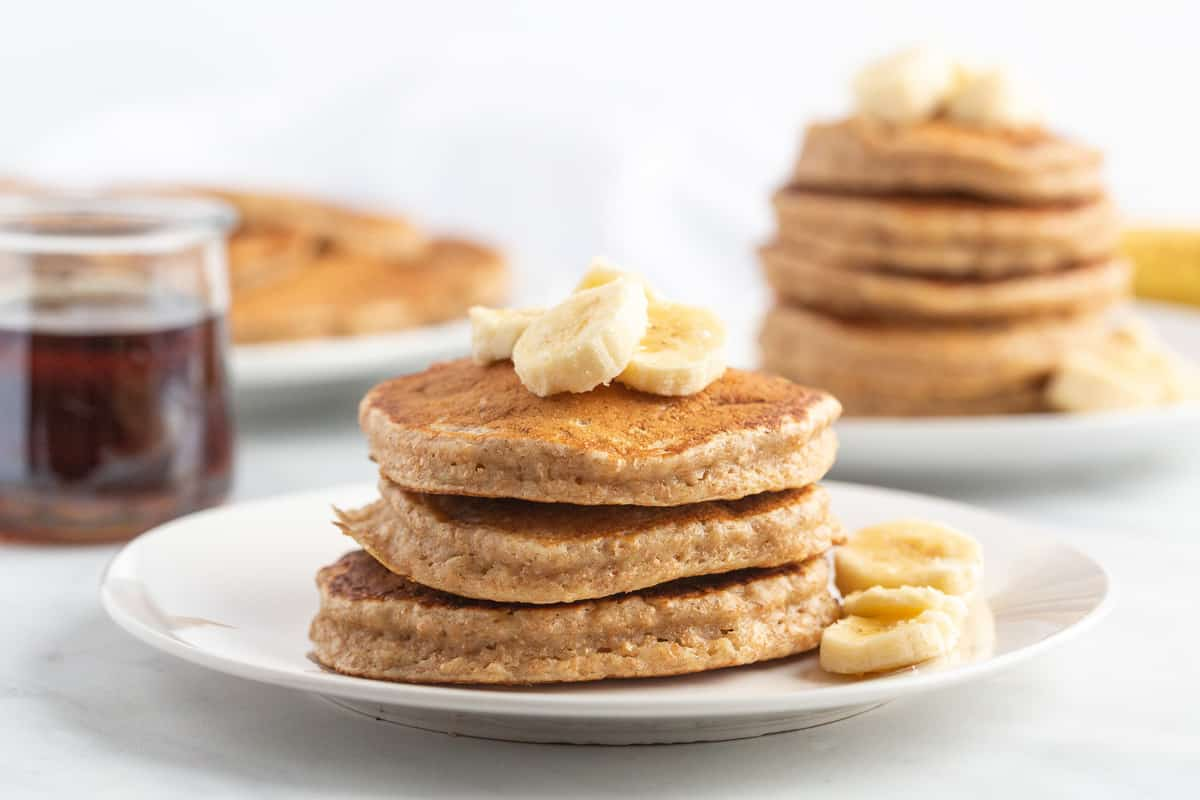 Two small stacks of pancakes with bananas.
