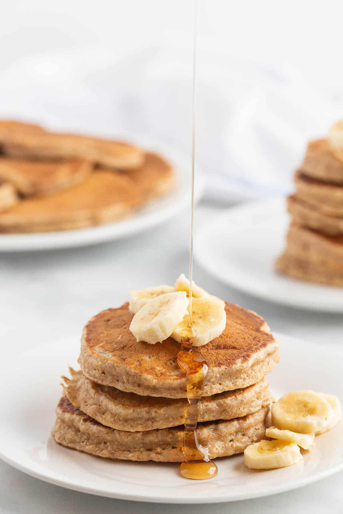 Stack of banana pancakes topped with banana slices and syrup.