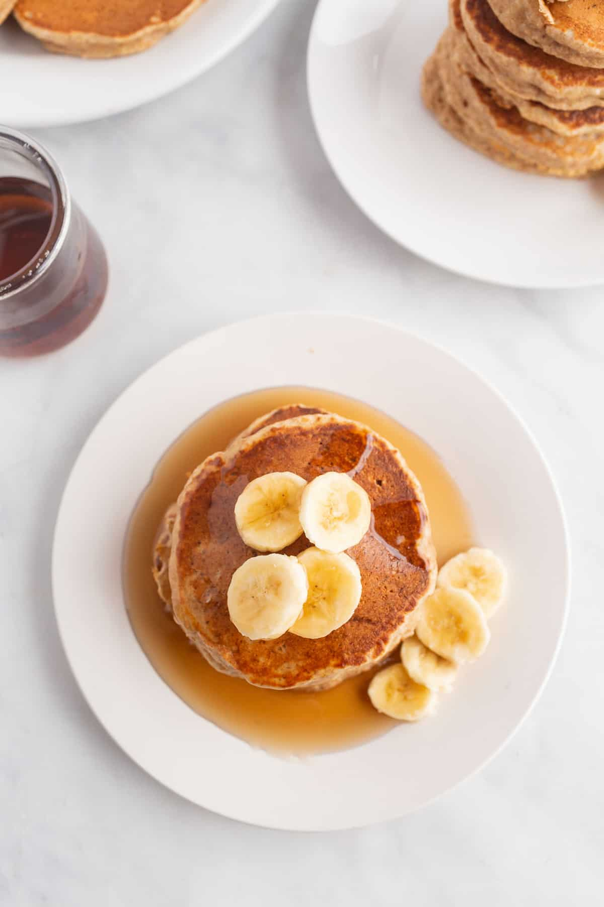 Overhead view of pancakes topped with syrup and bananas.