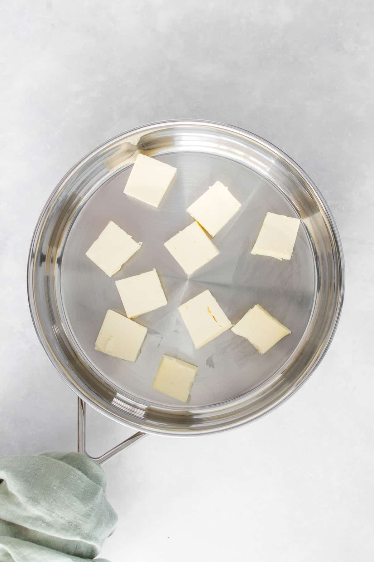 Cubed butter in a stainless steel saucepan/