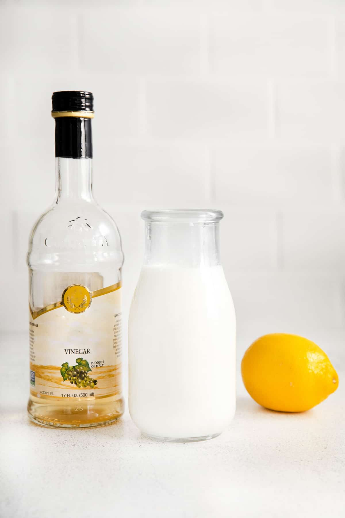 From left to right, a bottle of vinegar, a jar of milk, and a lemon.