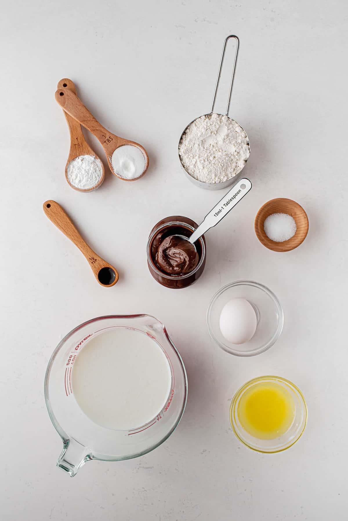 Overhead view of ingredients: flour, butter, vanilla, salt, baking powder, egg, buttermilk, nutella, and more.