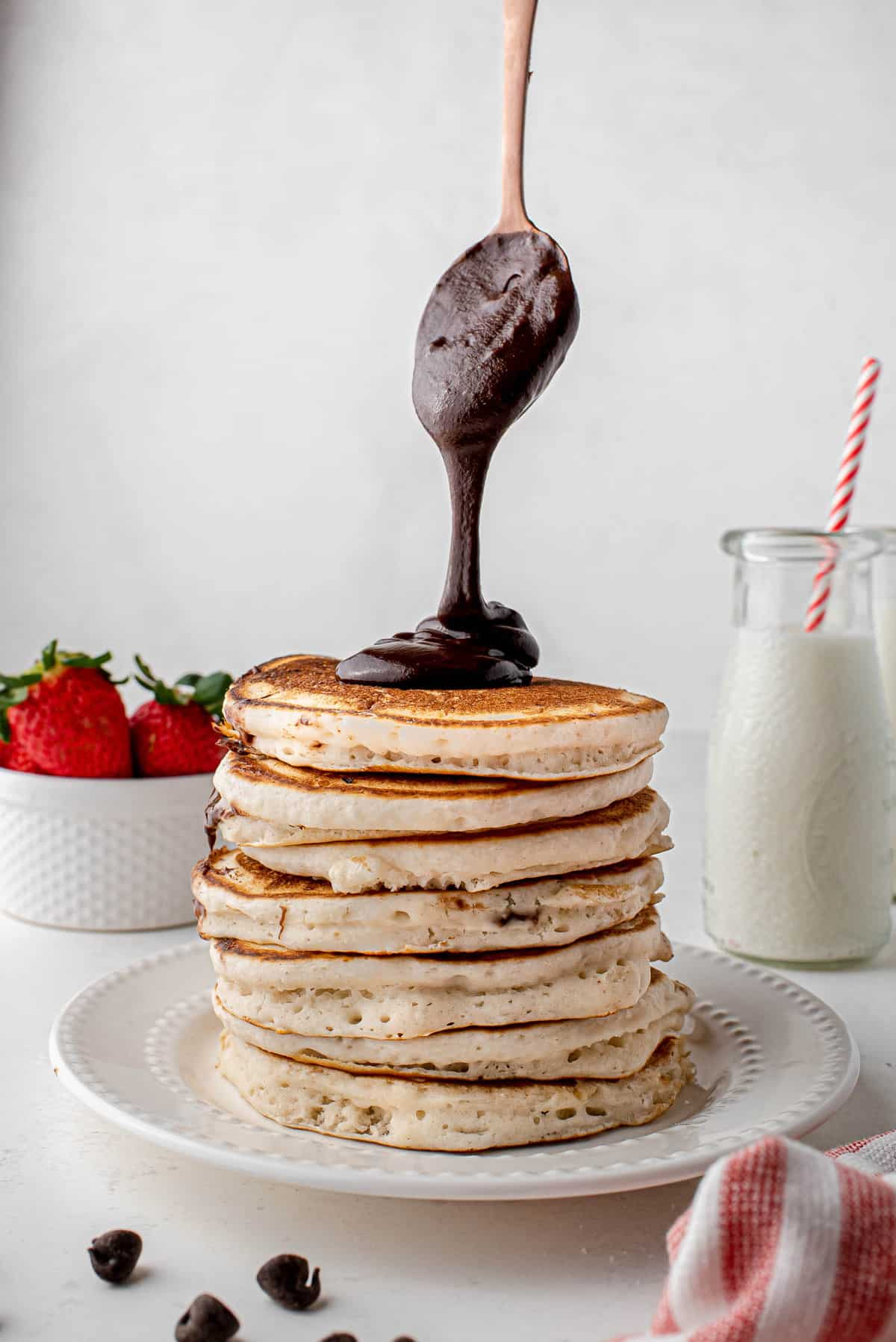 Nutella being spooned on a tall stack of pancakes.