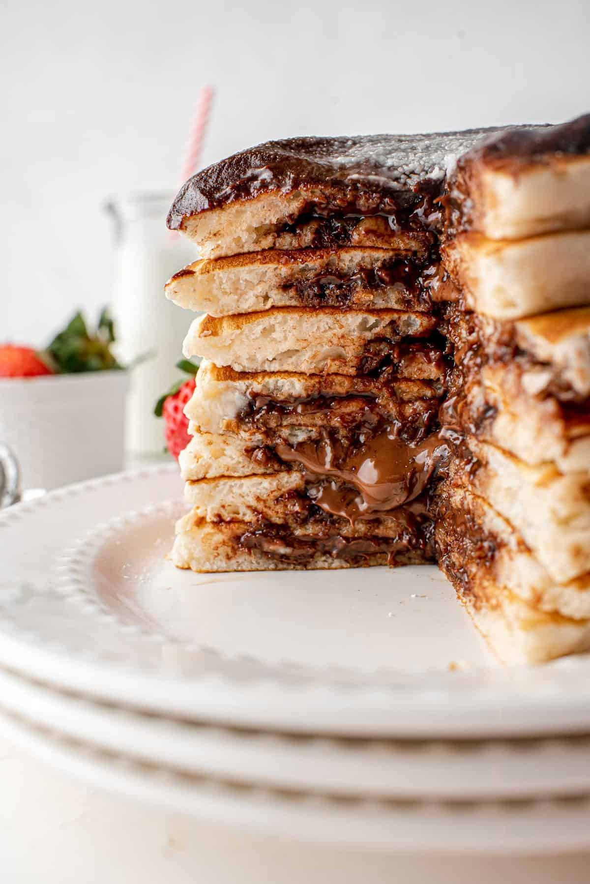 Stack of pancakes cut open to show nutella filling.