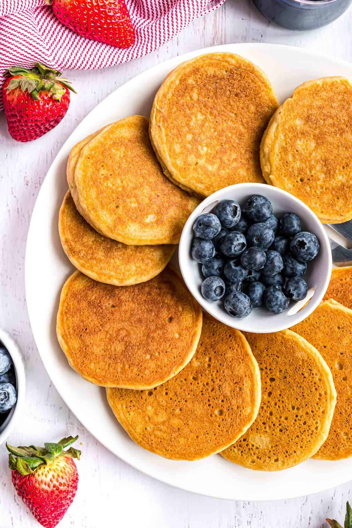 Overhead view of pancakes on a platter surrounding a bowl of blueberries.