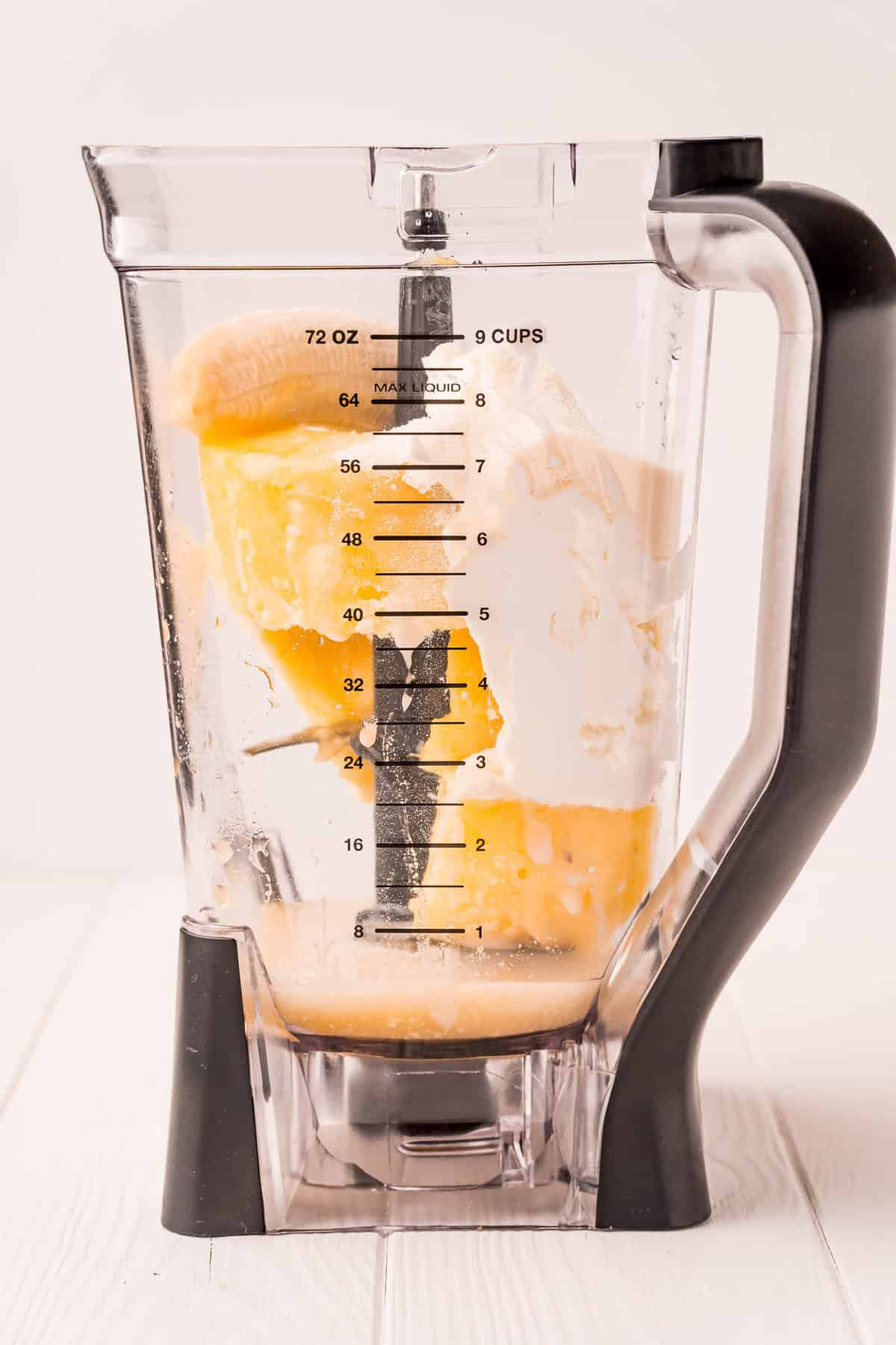 Straight on view of blender, with unblended ingredients.