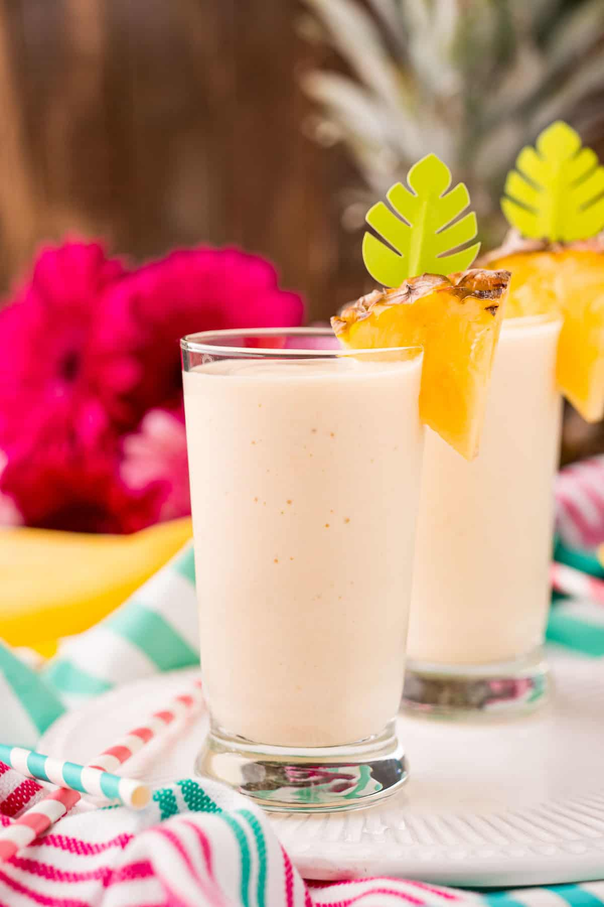 Two tall glasses with pineapple smoothie, topped with fresh pineapple.