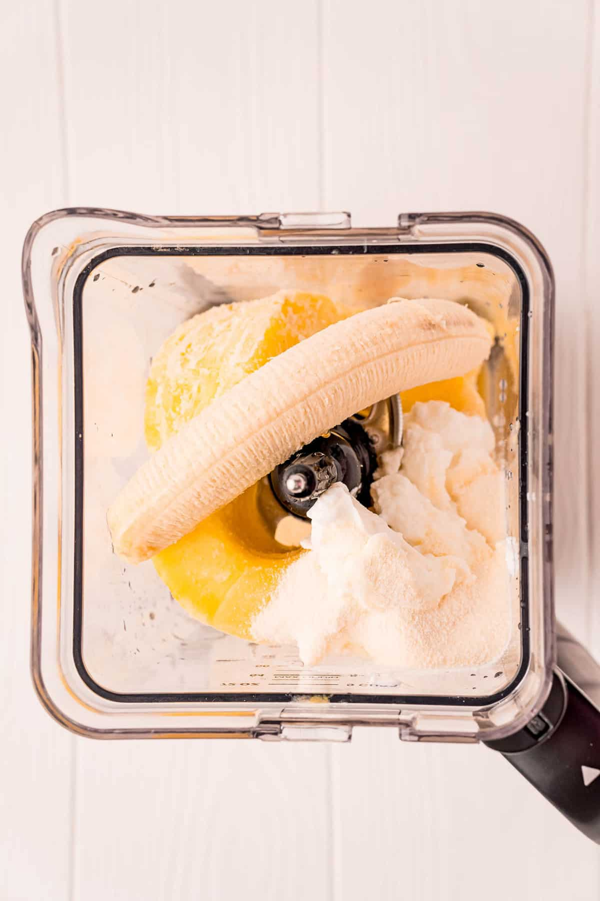 Overhead view of blender with banana, yogurt, and more.