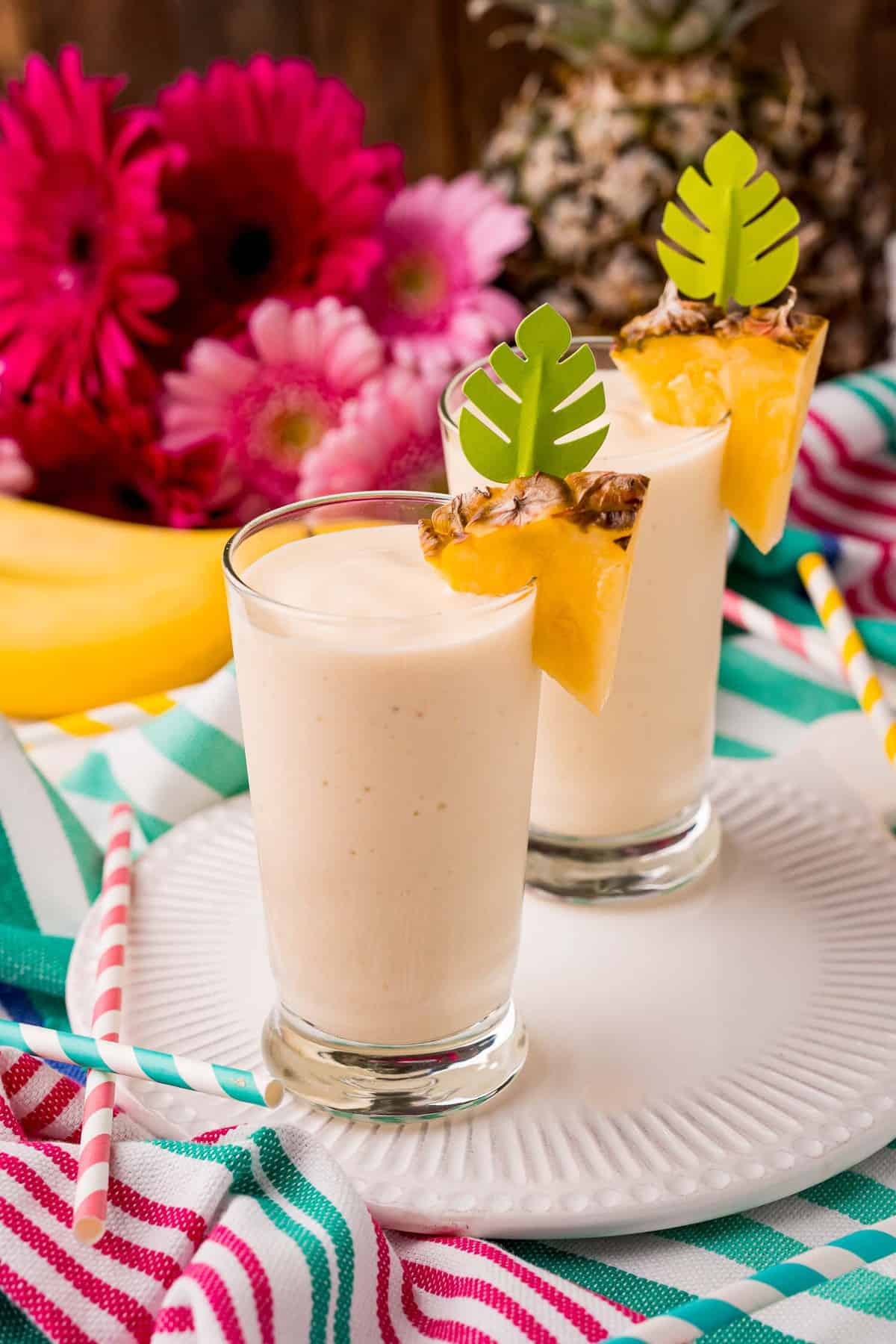 Two glasses with smoothies, against a bright colored background.