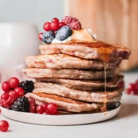 stack of raspberry pancakes topped with fruit and syrup.